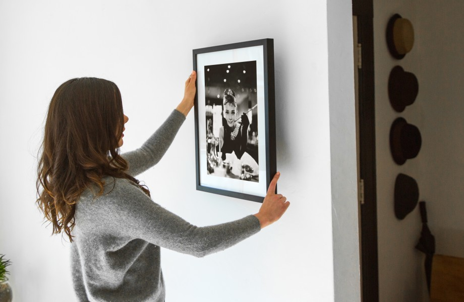 A woman hangs an Art.com framed print