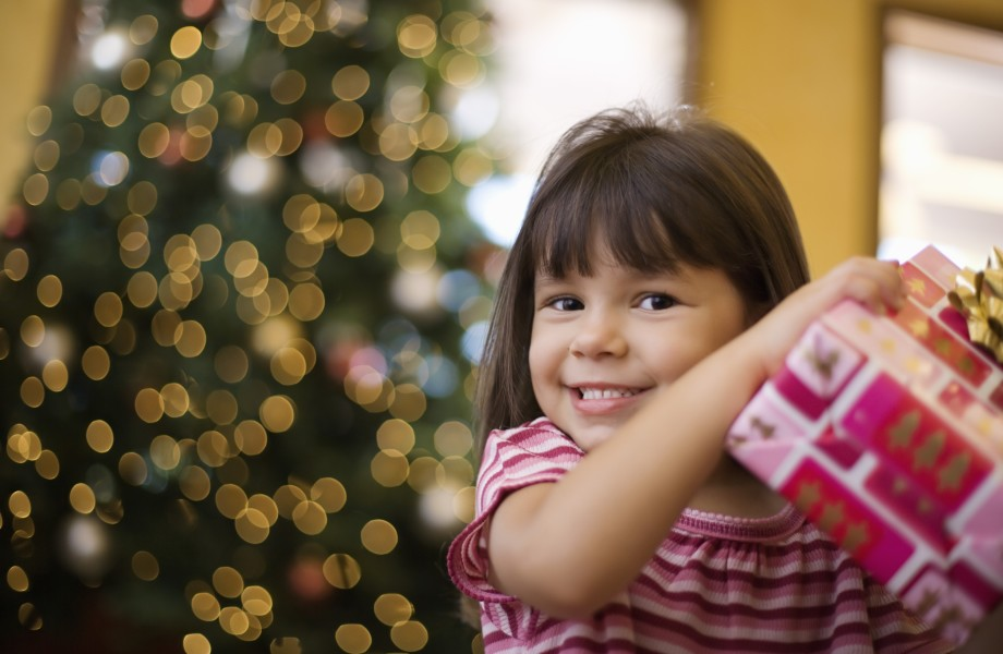 A young female child opening a Christmas gift