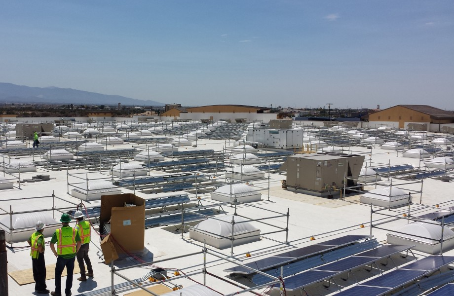 Solar power panels are spread across a store rooftop