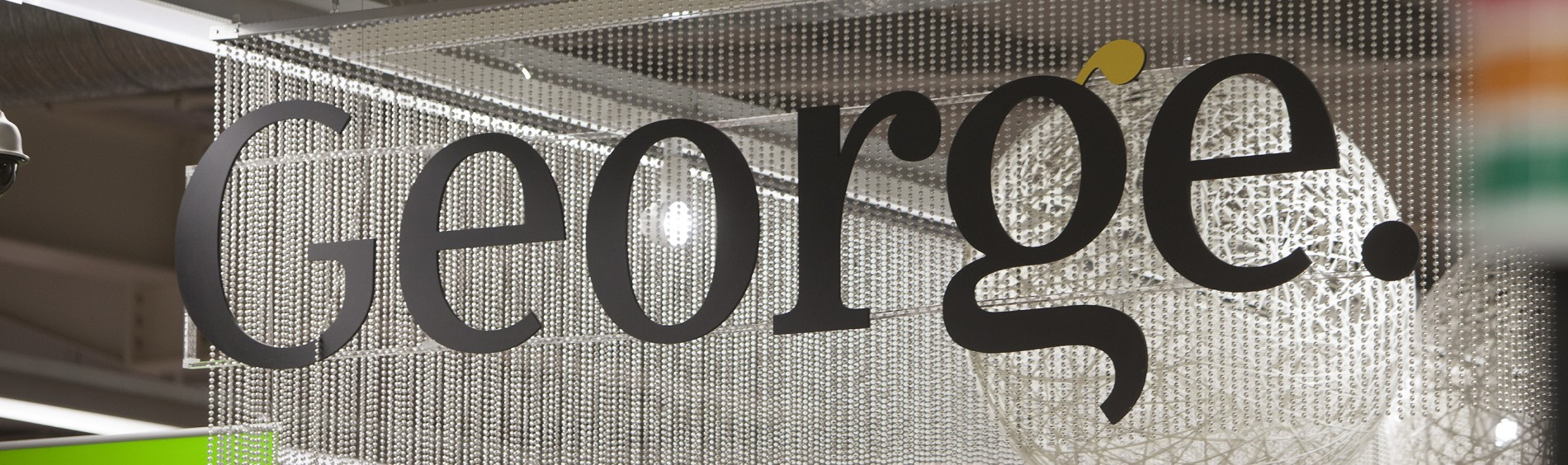 "A department sign hangs from the ceiling and reads ""George."""