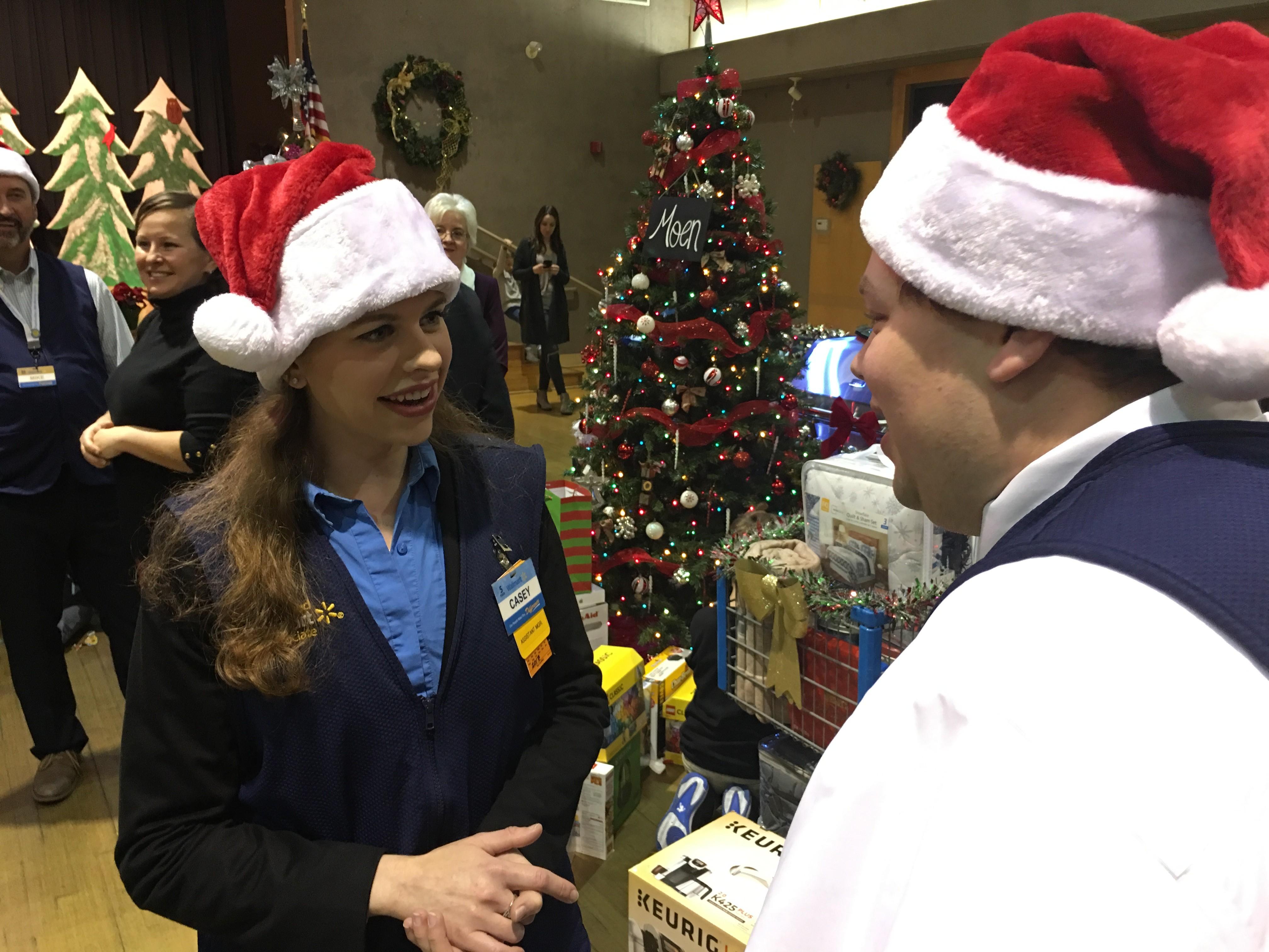 Associates talking in Santa hats near a Christmas tree