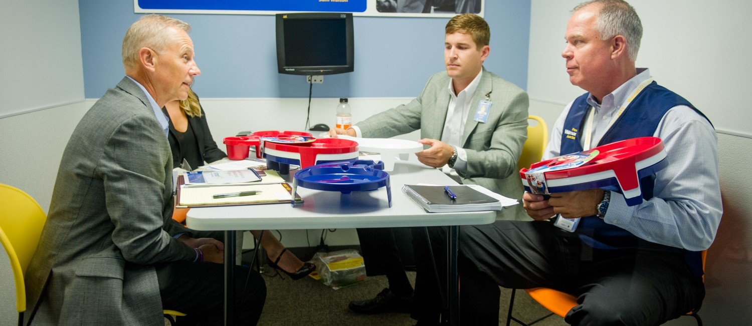 Three men and one woman meet at a table. Red, white and blue plastic trays are sitting on the table.