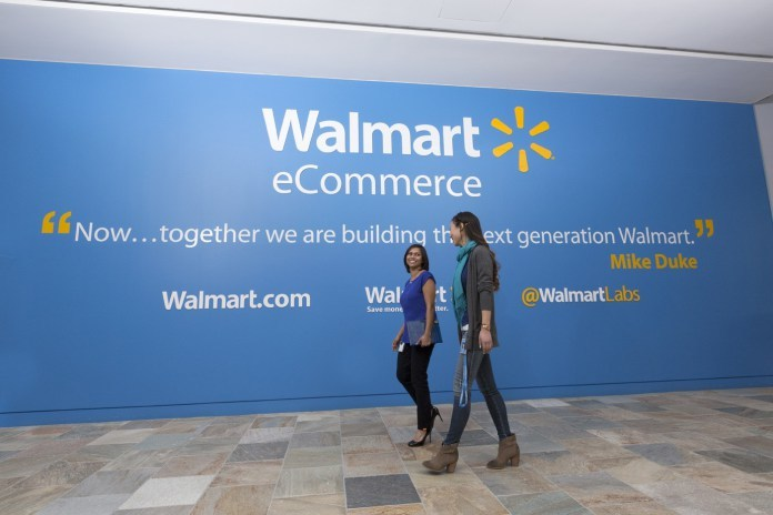 Two Associates walk by a Walmart eCommerce quote wall