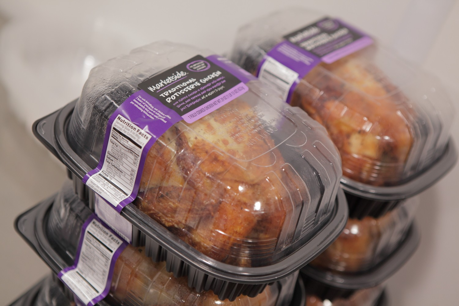 Two stacks of three rotisserie chicken packages with purple labels