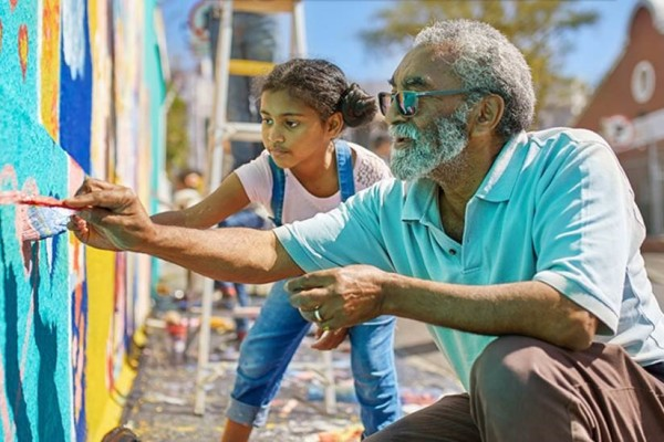 A man and a girl paint a mural