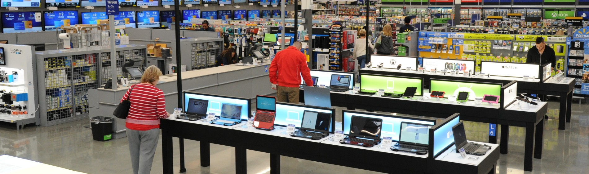 Two customers look on at laptops on tables