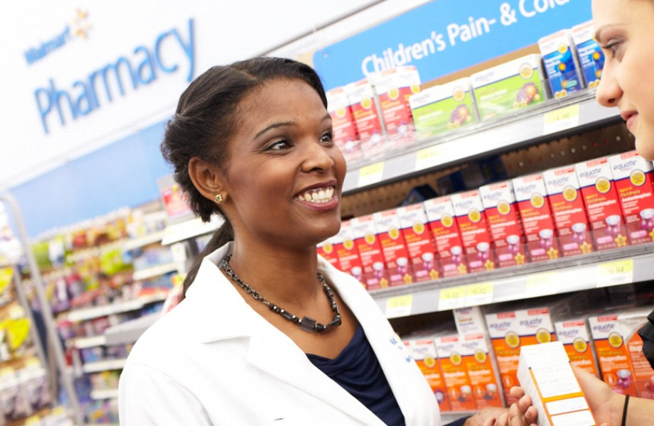 A pharmacist assists a customer in the children's medicine aisle