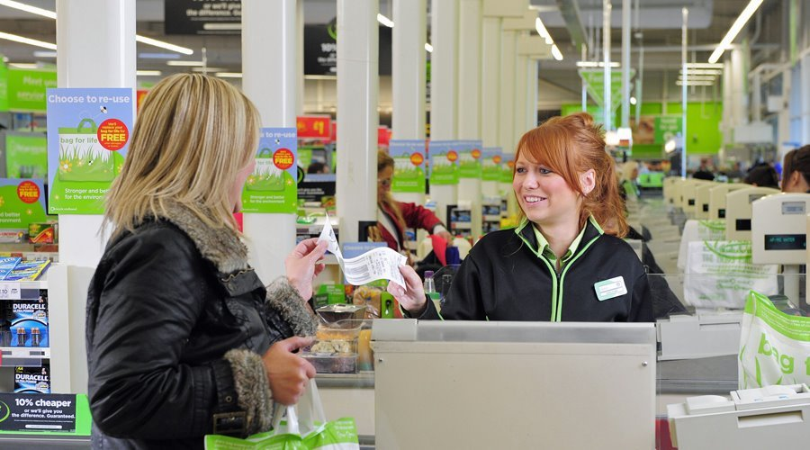 Asda cashier handing receipt to customer at checkout