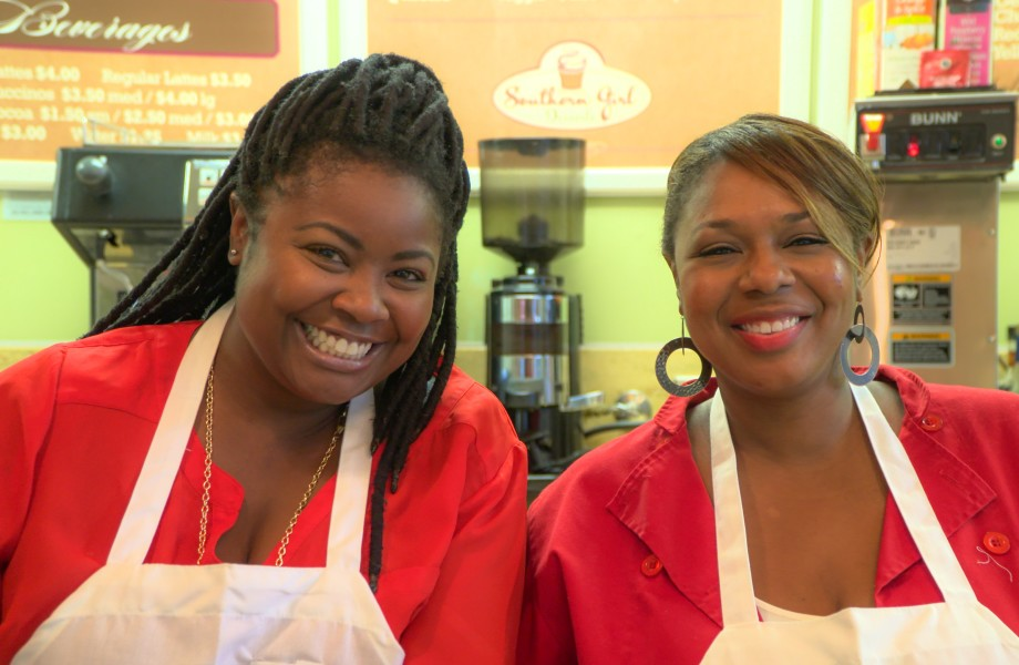 Two women smile sitting next to each other in white baker aprons