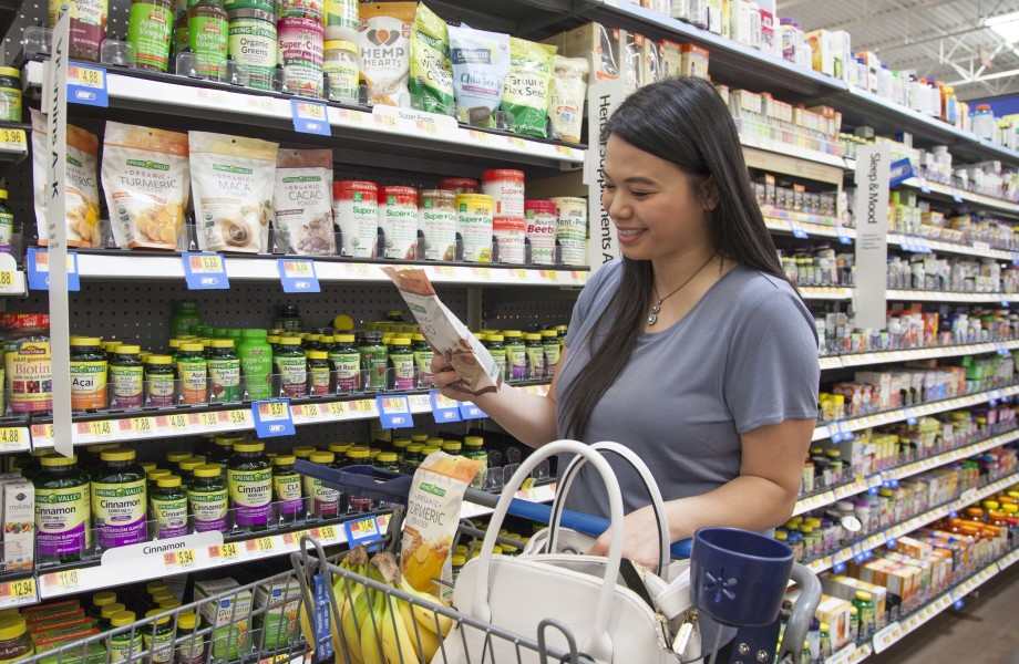 A customer shops a bag of vitamin powder in the health and wellness aisle in Walmart
