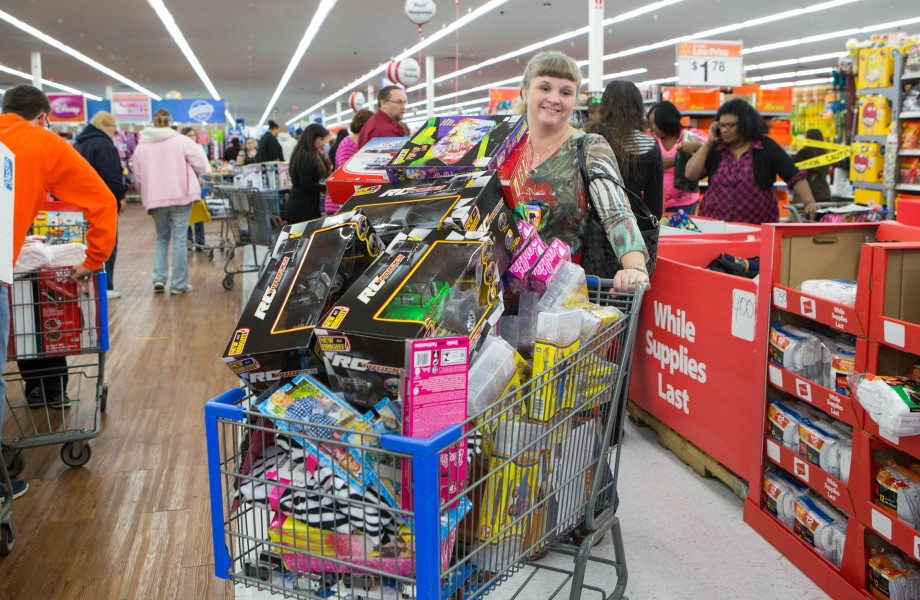 A female customer has a cart full of toys during a Black Friday event