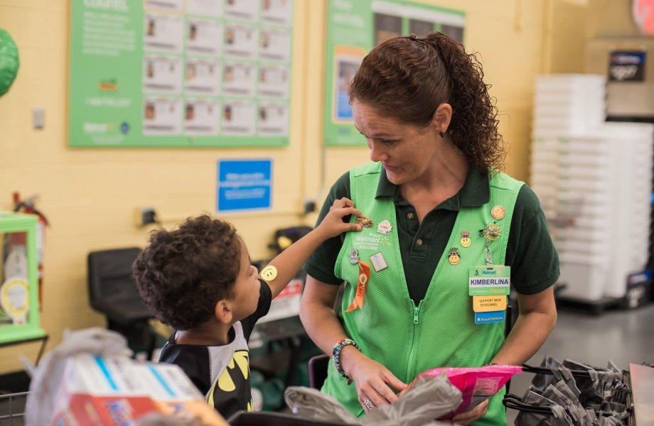 A Neighborhood Market associate wearing CMN Hospitals pins interacts with a child