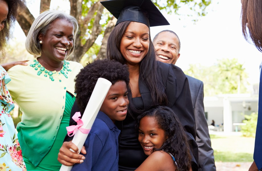 Graduate surrounded by family with diploma