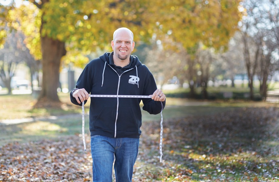Man in black sweatshirt holds tape measure on a bed of fall leaves