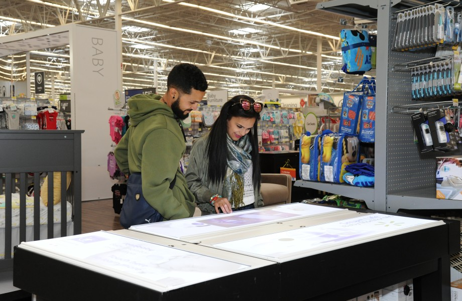 Customers shop online baby product assortment while in store on an interactive touchscreen table