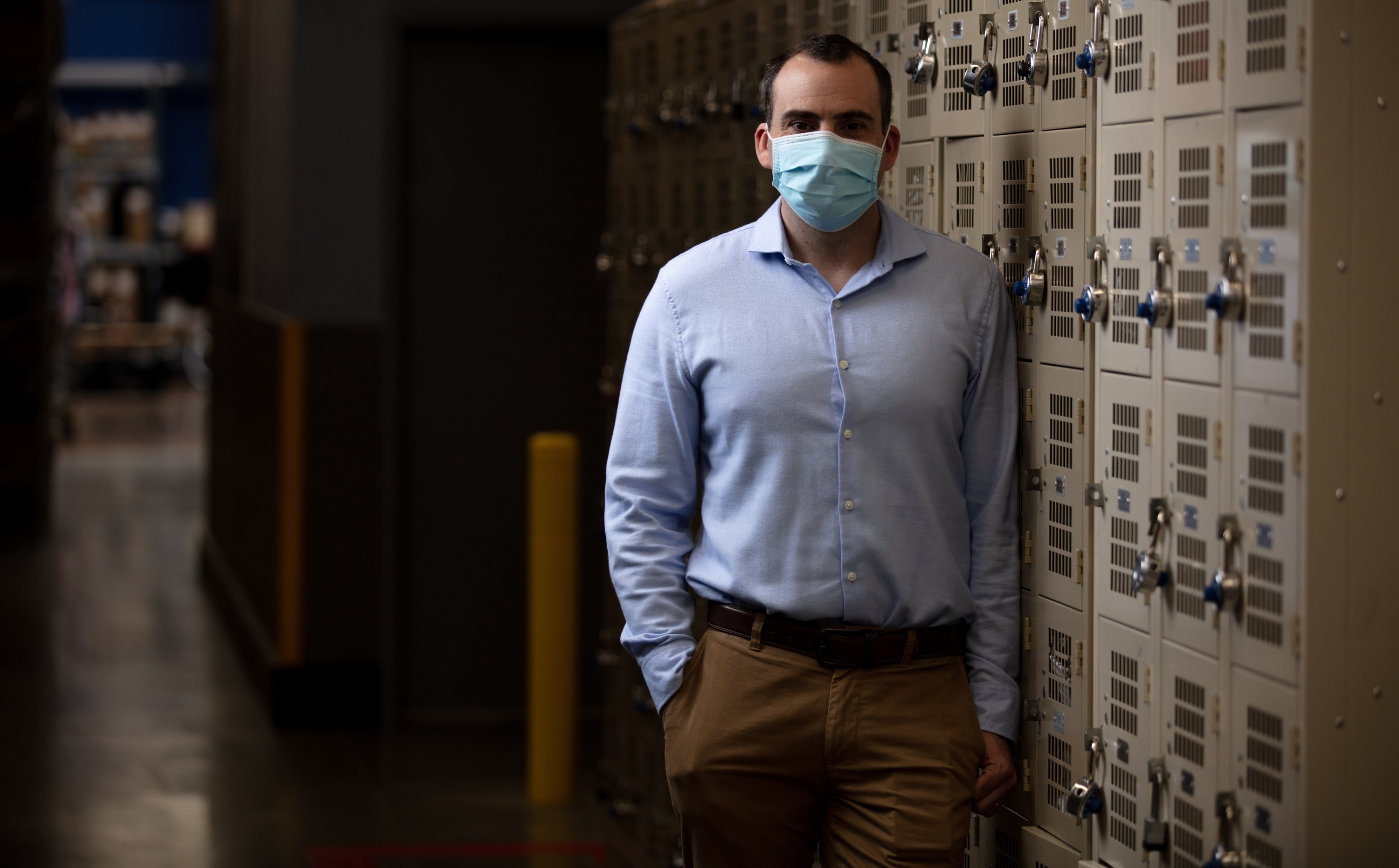 Drew Holler, senior vice president of associate experience and operations, wears a mask next to lockers
