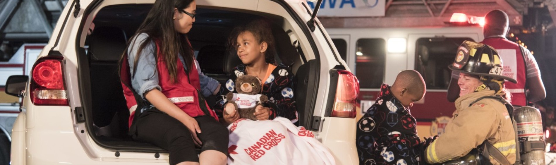 Smiling rescue workers comfort two children