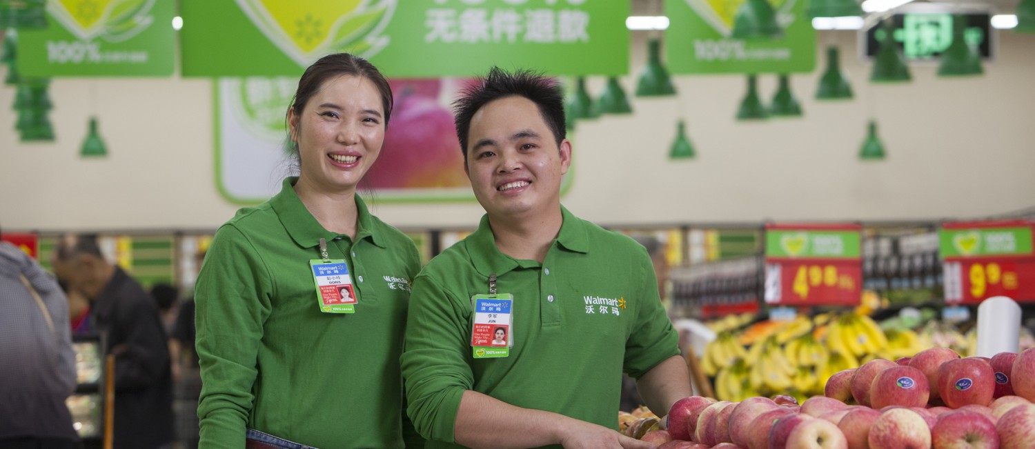 Two Walmart China associates stand beside an apple display