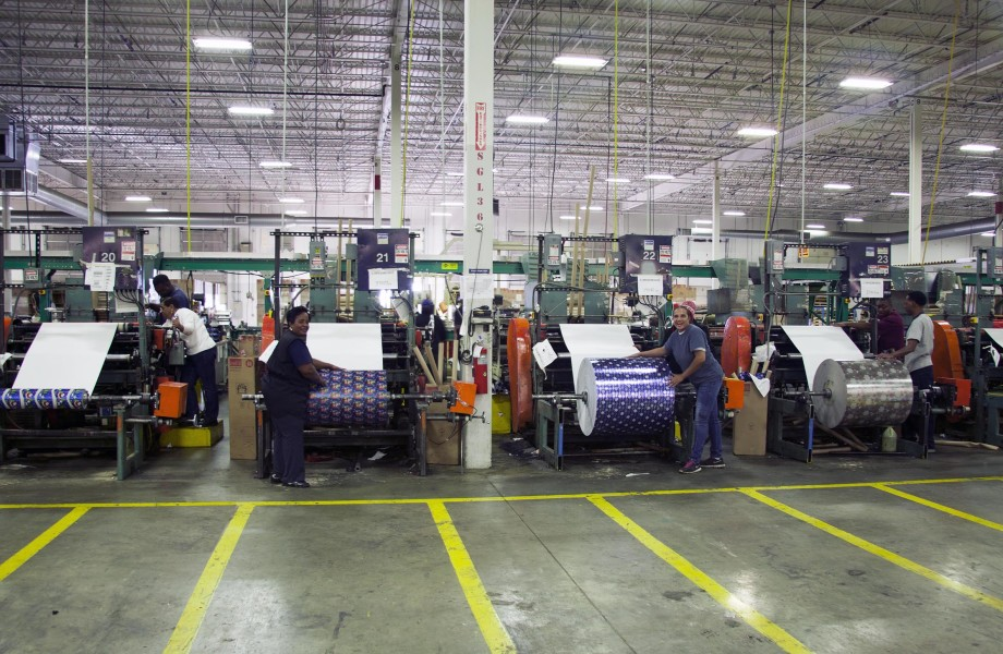 Employees are stand in front of large rolls of wrapping paper on rewinder machines inside a warehouse