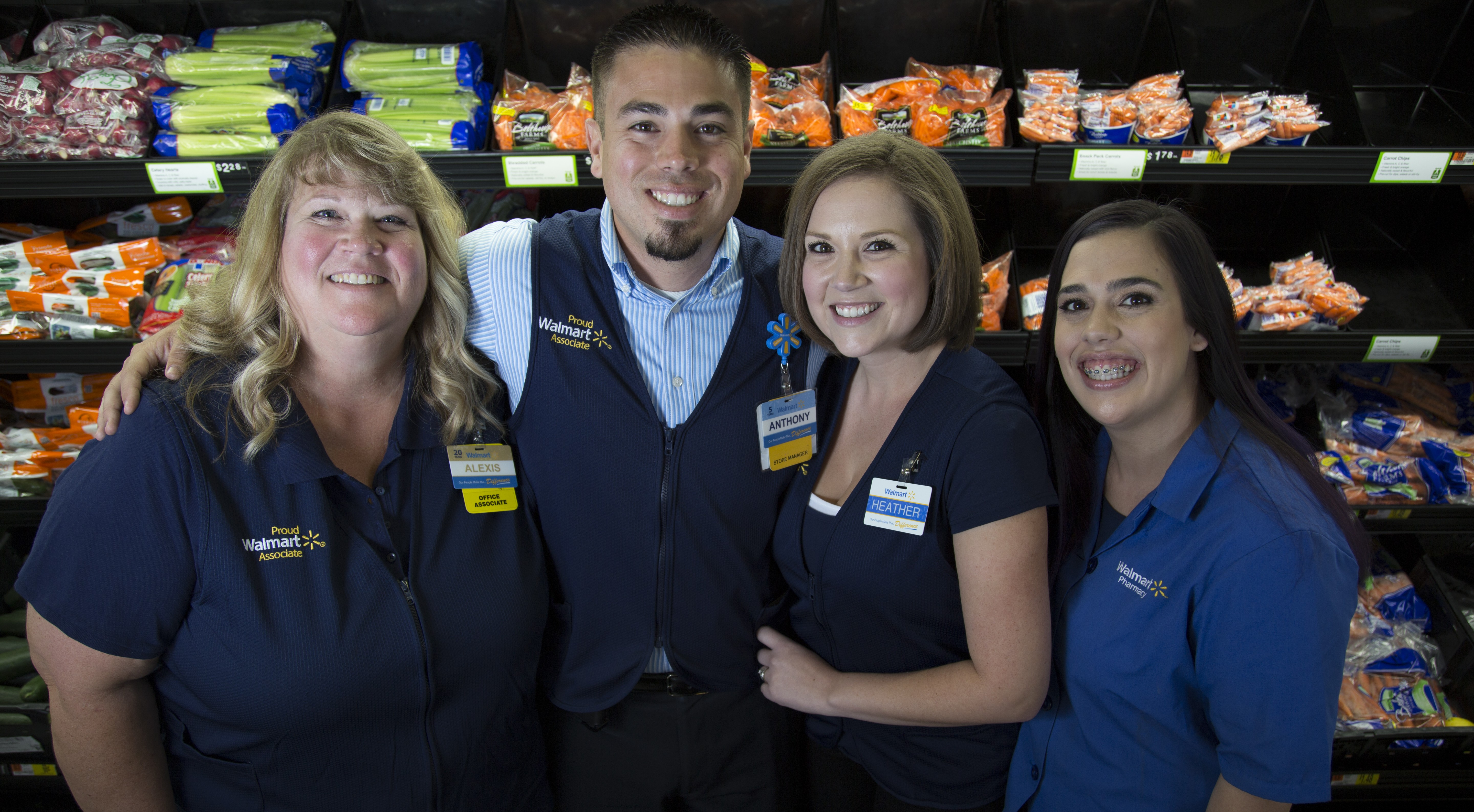 Four Walmart associates stand together with their arms wrapped around each other