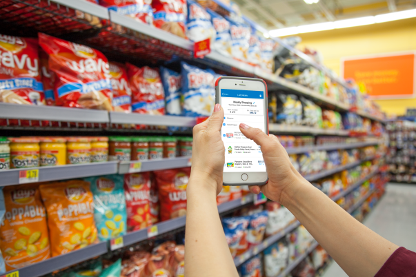 Customer shops in store using Walmart app on cell phone
