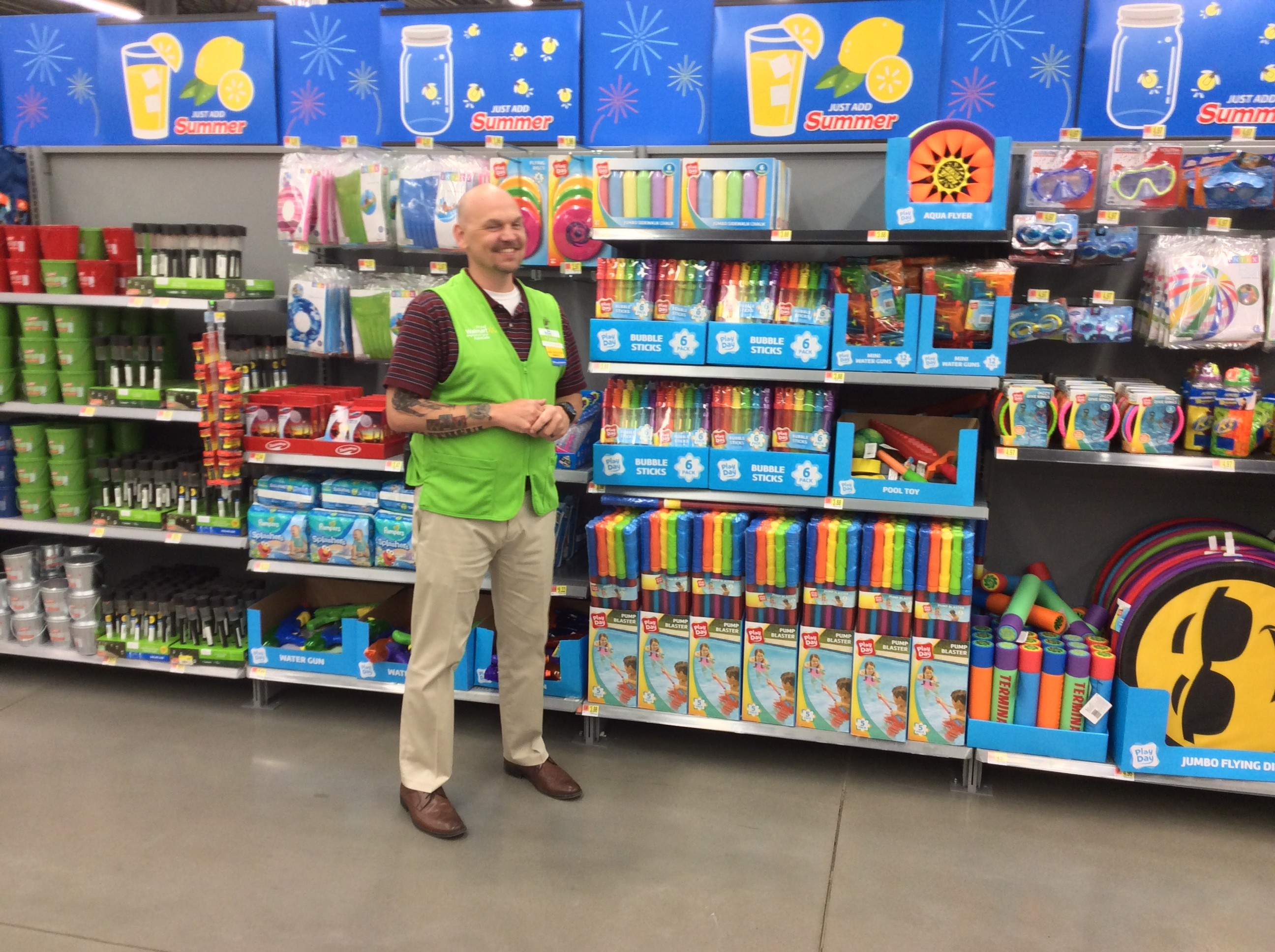 A male associate stands in front of shelves with outdoor toys