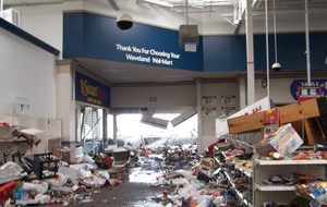 The entry  area to a Walmart store has products thrown on the floor and signs are hanging off the wall