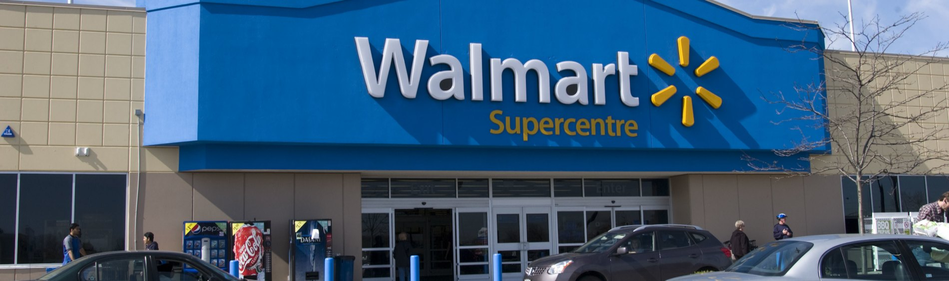 A Walmart Supercentre exterior view with cars from the parking lot