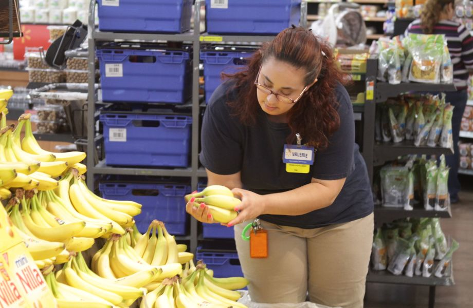 An associate selects products for Walmart Online Grocery