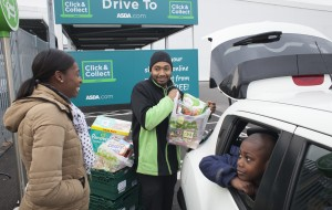 A colleague loads a family's groceries into their car