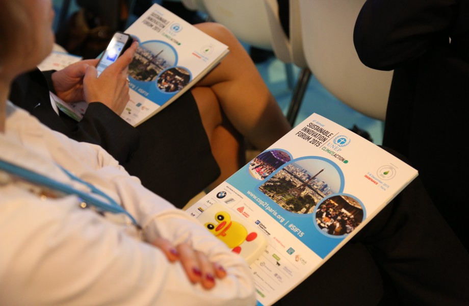A Sustainable Innovation Forum 2015 program booklet sits on a woman's lap