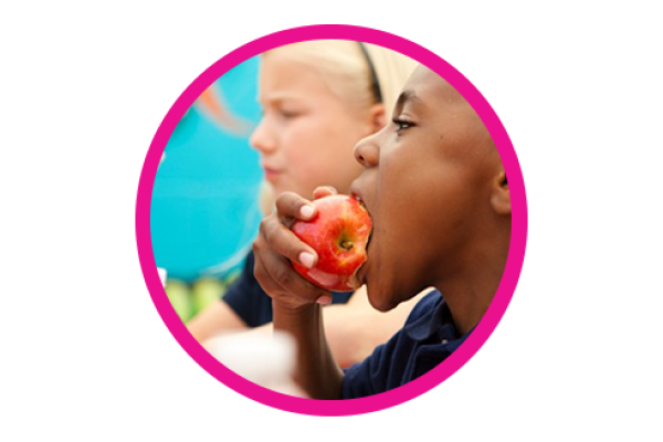 A boy eats and apple in the foreground while a girl eats and apple in the background