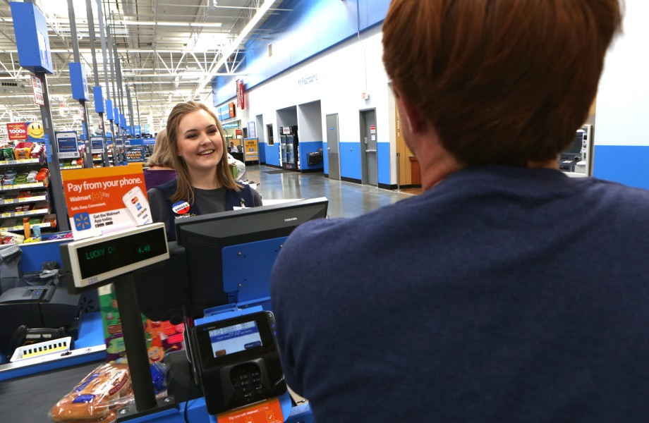 A Walmart associate smiles back at a customer during checkout