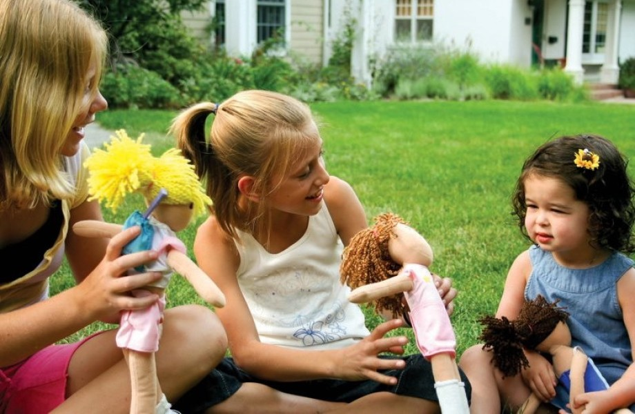 Three young girls of different ages are sitting cross-legged in grassy front yard playing each playing with their soft Go Go Sports Dolls.