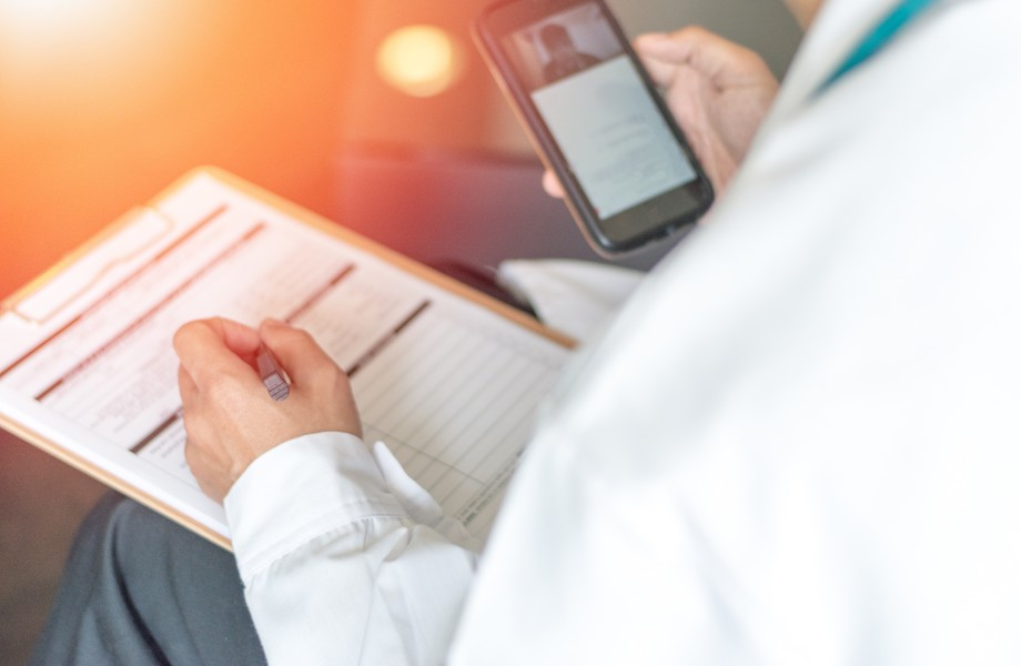 Doctor writing on chart while holding a phone - Telemed