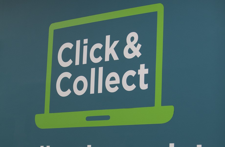 "A blue wall features a painted ""Click & Collect Collection Point"" sign"