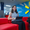 Walmart eCommerce associate Carrie Farber works on a tablet at the Walmart eCommerce office as her guide dog sits nearby