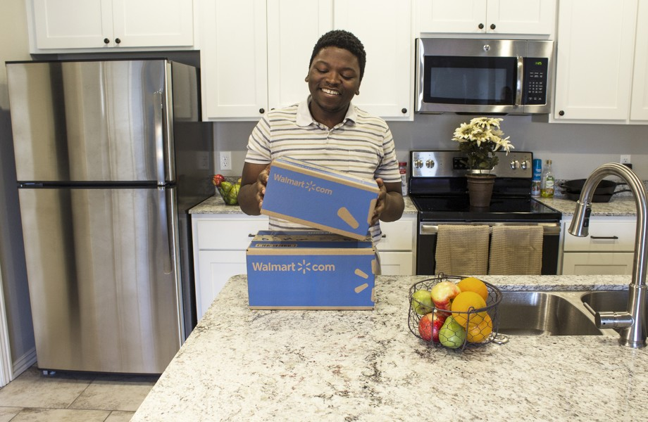 Customer picking up Walmart delivery boxes in his kitchen