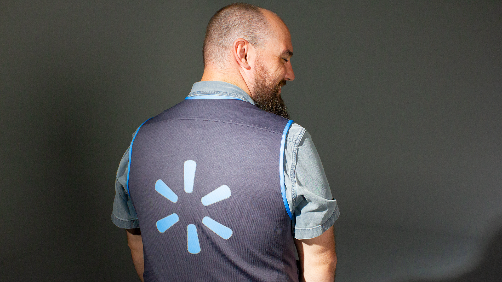 Associate wearing new blue vest showing back close up